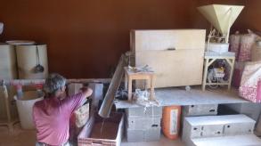 A droite: le moulin avec ses meules (non visibles). Au centre: le blutoir. A gauche: la vis d'ensachage de la farine